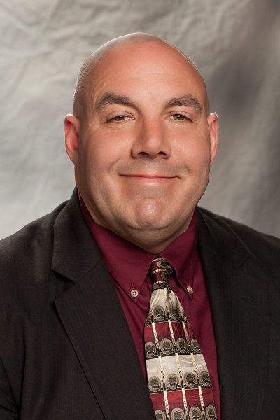 portrait photo of Chuck Pasquarell, a white man wearing a brown suit jacket with a maroon shirt and tie underneath