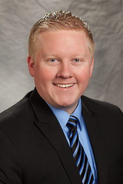 portait photo of Alvey Harrison, a man wearing a black suit, a blue button down shirt, and a striped tie