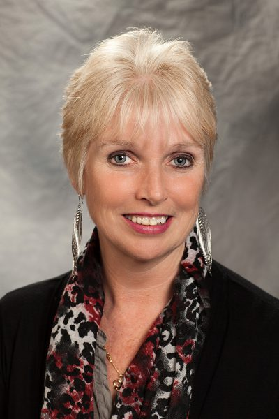 portrait photo of Annie McMahon, a woman with short blonde hair and feathered dangly earrings, wearing a zebra print shirt