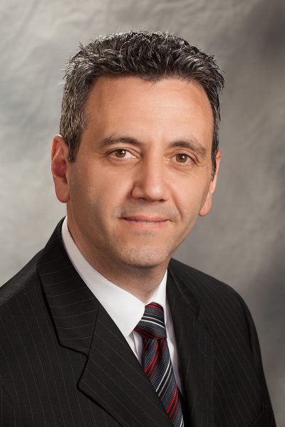 portrait photo of Dino Rosati, a man wearing a black suit jacket, and red, white, black, and gray striped tie
