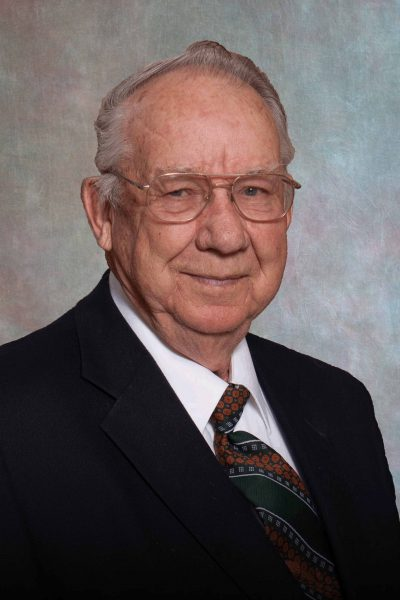 portait photo of Don Briner, a man with glasses wearing a black suit jacket, white shirt, and orange and green tie