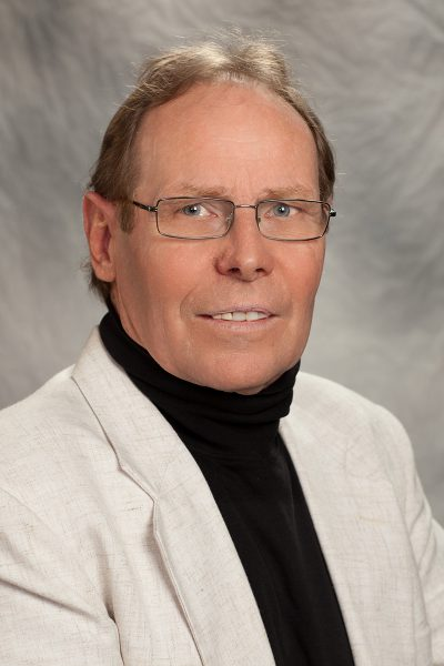 portrait photo of Harold Jones, a man with glasses wearing a black turtleneck and light colored suit jacket