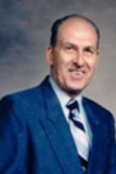 portrait photo of past HRCCU board president William Marcoux smiling and wearing a dark blue suit jacket