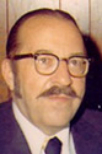 candid photo of Wilson Smead, a previous HRCCU board president with brown thick-rimmed glasses and a mustache