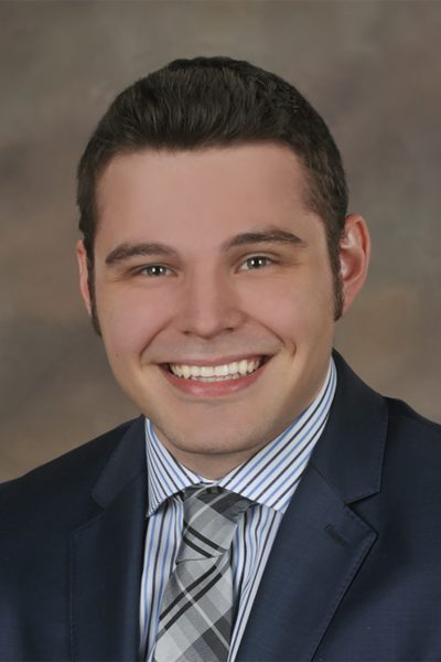 portrait photo of Scott Loesch, a man with brown hair wearing a gray suit jacket and white, black, and blue striped shirt