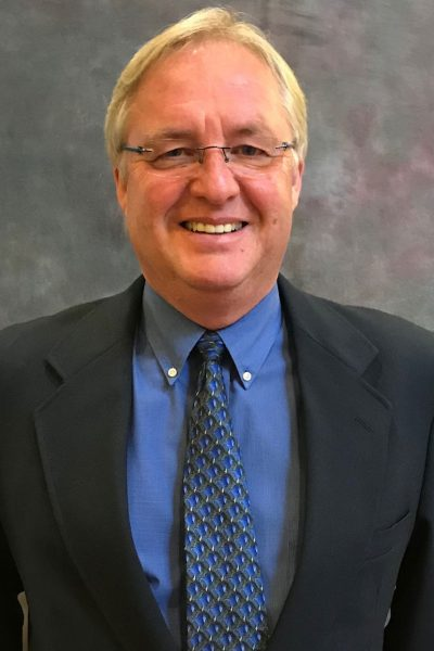 portrait of Tom Welch, a member of the HRCCU Supervisory Committee, wearing a blue shirt and blue patterned tie