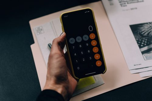 smartphone with the calculator app opened held in an adult's hand above a manilla folder with tax paperwork