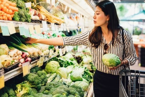 adult woman with dark brown hair wearing a black and white striped blouse shopping for fresh produce at a grocery store