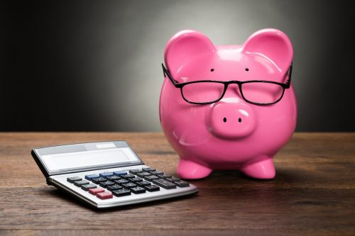 pink piggy bank wearing black plastic glasses on a wood table next to a calculator