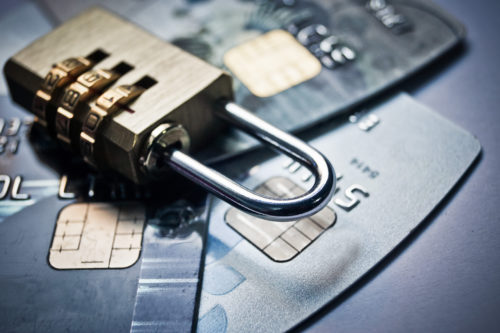 gold lock laying on top of three dark gray-colored chip credit cards