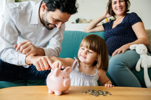 father helping young daughter put change in light pink piggy bank on a light brown wood table