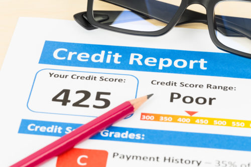 poor credit report resting on a wood table beneath a pair of black, plastic glasses and a pink pencil with graphite tip