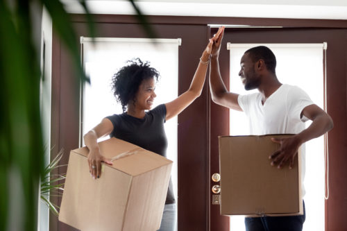 adult man and woman giving each other a high-five while holding moving boxes standing inside their new home