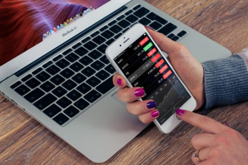 woman with pink and purple painted fingernails holding a white iPhone looking at the stock market rates