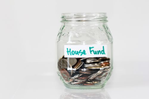 loose change in a glass jar with a white label that says house fund in green letters