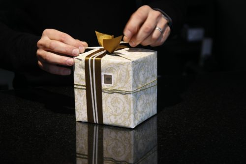adult man wearing a black sweater tying a gold bow on a holiday gift wrapped in gold and white wrapping paper