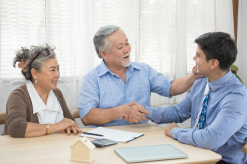 older man and woman sitting at a wooden table with financial paperwork shaking the hand of a retirement planning financial advisor