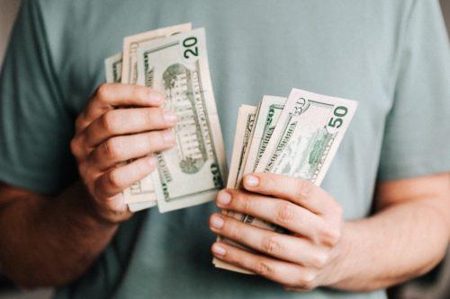 man wearing a blue tee shirt holding United States money to make a deposit