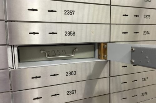 two rows silver of safety deposit boxes with numbers and two keyholes on the doors