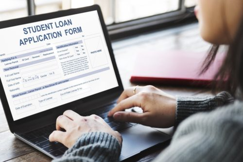 woman with black hair wearing a gray sweater filling out a student loan application on a gray laptop