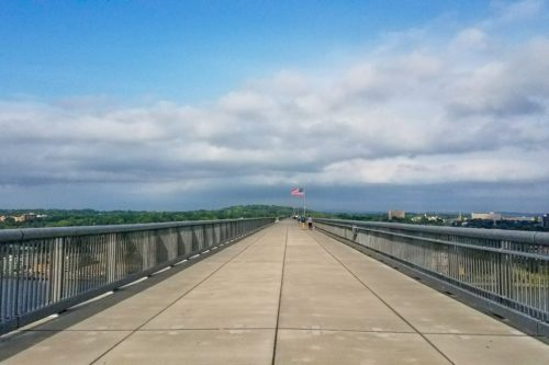 Walkway Over the Hudson walking bridge on a sunny day with white clouds in the sky and an American flag marking the halfway point of the bridge