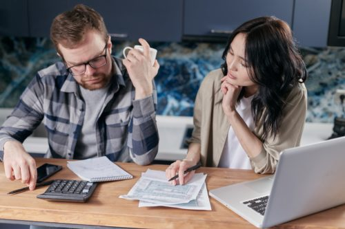 adult man holding a white coffee mug sitting next to an adult woman looking for financial paperwork next to a black calculator and silver laptop